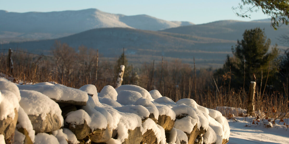 stone wall in winter with mountains in background
