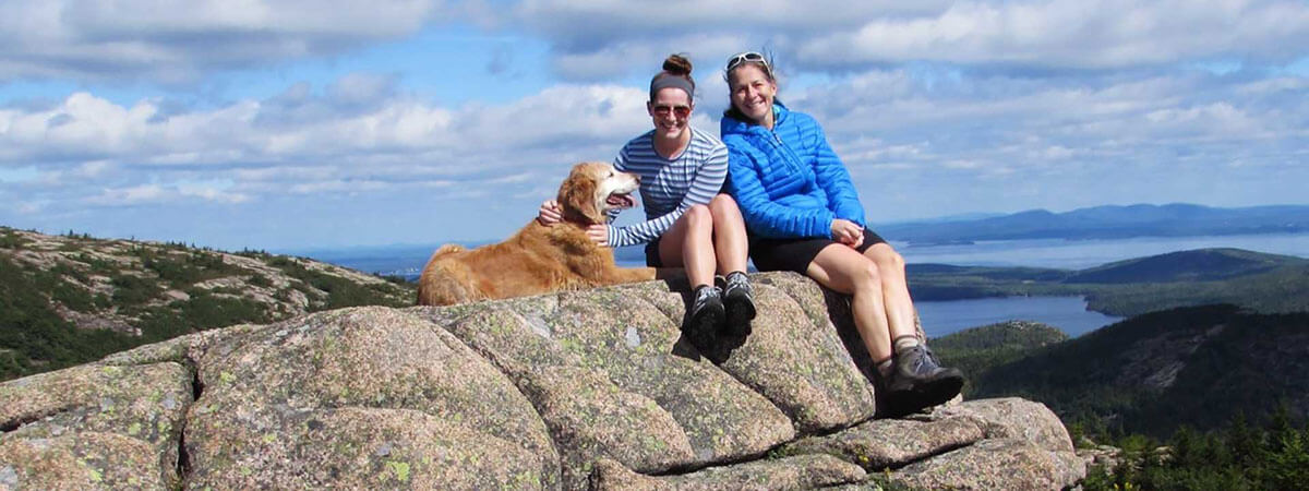 two women and a golden retriever on a mountain top